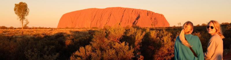 Smiling girl watching sunset over Uluru